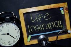 Life Insurance handwriting on chalkboard on top view. stock image
