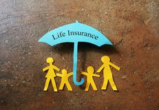 Life Insurance paper family. Paper family of four under a Life Insurance paper cutout umbrella Stock Photo