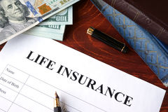Life insurance policy. And currency on a table Stock Images