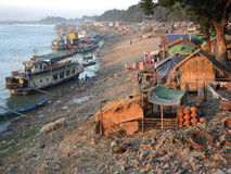 Daily life on Irrawaddy riverbank in Mandalay, Burma. Riverbank with boats and pigs Stock Images