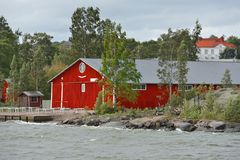 Life on islands. Red wooden houses on island in front of Helsinki Stock Photos