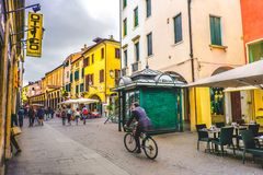 Daily life in Italy business man bicycle downtown roads Padua green newsstand kiosk street. Daily life in Italy. A business man in bicycle crossing one of the Royalty Free Stock Image