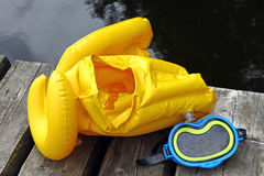 Life jacket and diving mask. Yellow life jacket and diving mask for children on lake bridge Royalty Free Stock Images