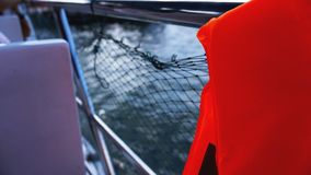 Life jacket and net on boat. Safety net on boat. Ropes on boat. Safety ropes and blue sea. Waves on the sea and safety mesh stock image