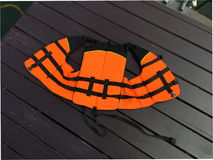 Life jacket. Orange life jacket on the wood floor royalty free stock image