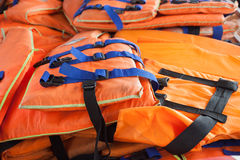 Life jacket. Pile of orange reflective life-jackets royalty free stock image