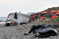 Life Jackets and boats left on Greek beach by refugees Royalty Free Stock Images