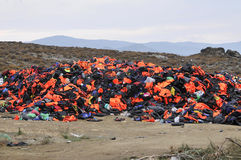 Life Jackets and boats left on Greek beach by refugees Royalty Free Stock Image