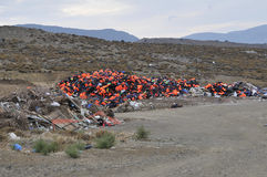 Life Jackets and boats left on Greek beach by refugees Stock Images