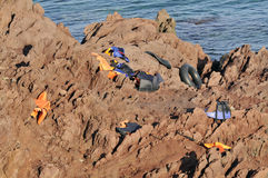 Life Jackets and boats left on Greek rocks by refugees Stock Images