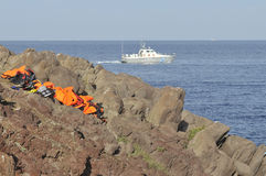 Life Jackets and boats left on Greek rocky beach and the Greek coastguard Royalty Free Stock Images