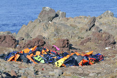 Life Jackets and boats left on Greek rocky beach by refugees Royalty Free Stock Image