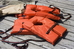 Life Jackets. Bright orange life jackets drying on wooden deck royalty free stock photos