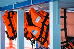 Life jackets on marine tourism boats. Sea, travel, summer, nature, orange, ocean, water, outdoors, bay, ship, tourist, landscape, safety, security, recreation stock images