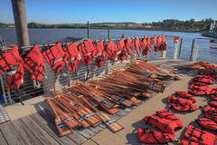 Life Jackets for Safety and Oars. Red life jackets and oars are waiting and ready for pick up by racers in the National Harbor Dragon Boat Regatta on the Potomac Royalty Free Stock Photography