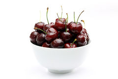 Life is Just a Bowl of Cherries. Dark red wet cherries in a white bowl on a white background stock image