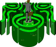 Life Labyrinth. A business professional looks in the distance trying to find his way out of a labyrinth Royalty Free Stock Image