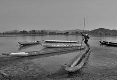 Daily life on Lak lake. The man rows across the Lak lake to begin his work in the farm Royalty Free Stock Images