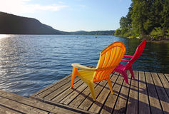 Life at the lake. Picture of two adirondack chairs on a floating dock at St Mary Lake on Salt Spring Island,BC,Canada Royalty Free Stock Image