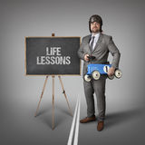 Life lessons text on blackboard with businessman Royalty Free Stock Photography
