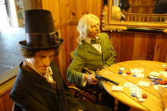 Life-like dummies depicting the wild west. Fake, realistic figures dressed to kill around a poker table in a wild west saloon in dakota Royalty Free Stock Photography