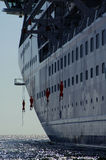 Life Lines. Cruise ship lifeboat lines dangling from the side of the boat Royalty Free Stock Photo