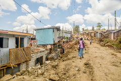 Daily life of local people of Kibera Slum in Nairobi,Kenya. Nairobi, Kenya- March 5,2016: Woman walking down the dirt road of Kibera Slum in Nairobi,Kenya stock photos