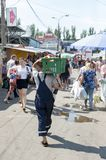 Daily life at the market. Man carries box on his shoulders, in the crowd of the central market of chisinau Moldova royalty free stock photography
