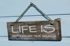 Life is... Message `Life is better at the beach` on the wooden board stock photos