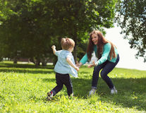 Life moment of happy family! Mother and son child playing. Having fun together on the grass in sunny summer day Royalty Free Stock Photo