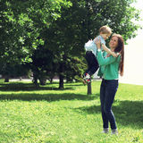 Life moment of happy family! Mother and son child playing. Having fun together outdoors at the weekend on the grass in sunny summer day Stock Photos