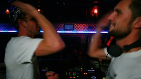 Life in a nightclub two DJ rocking the crowd of dancing people give five stock footage