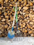Life off the grid. Garden spade, fork and woodpile for heating. Royalty Free Stock Photography