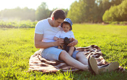 Life portrait of father and son sitting together on the grass Stock Photos