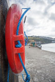 Life preserver belt. A red life preserver belt fixed to the wall at Mevagissey Harbour Royalty Free Stock Photos