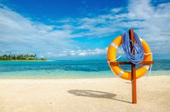 Life preserver on exotic sandy beach. With blue sky Royalty Free Stock Image