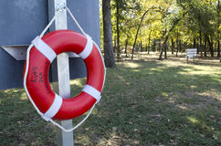Life Preserver Hanging In The Park. A red life preserver haning on a sign by the swimming area in the park Stock Image