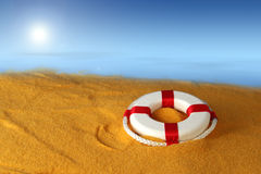 Life preserver for help. Life preserver for first help on the yellow sand background Stock Photo