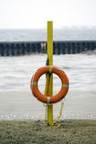 Life preserver ring hanging from yellow emergency pole on empty. Beach in winter Royalty Free Stock Photography