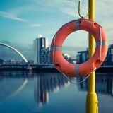 Life Preserver Beside the River Clyde, Glasgow Scotland. Orange Life Buoy With River Clyde and Arc Bridge in the Background Royalty Free Stock Photography