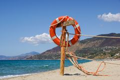 Life preserver on sandy beach somewhere near at sea.  Stock Image
