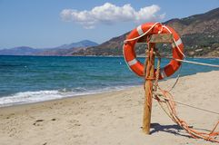 Life preserver on sandy beach somewhere near at sea.  Royalty Free Stock Photography