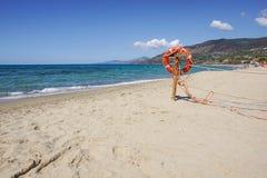 Life preserver on sandy beach somewhere near at sea Stock Photo