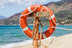 Life preserver on sandy beach somewhere near at sea.  Royalty Free Stock Images
