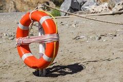 Life preserver on sandy beach somewhere near at sea Royalty Free Stock Photo