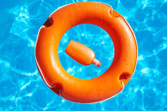 Life preserver  and sunblock. Bright orange life preserver floating on the surface of blue water and sunblock Royalty Free Stock Image