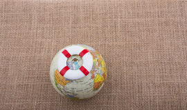 Life preserver on top of globe. On canvas background Royalty Free Stock Photo