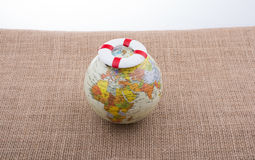 Life preserver on top of globe. On canvas background Stock Image