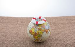 Life preserver on top of globe. On canvas background Royalty Free Stock Photos