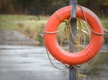 Life preserver by water's edge. Life preserver by side of river. River is visible in background Stock Images